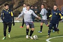 Kanonýr Votic Marek Štork (v bílém) se snaží dostat z obležení dvou hráčů Želče.