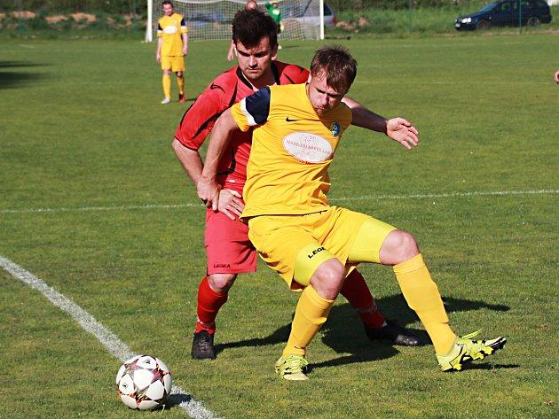 Divišovský střelec třetí branky Marek Hanuš (ve žlutém) si kryje míč před zdislavickým Davidem Jankovským.
