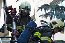 Rychlý příjezd vysokozdvižného žebříku hasičů a zásah při požáru paneláku komplikují zaparkovaná auta.