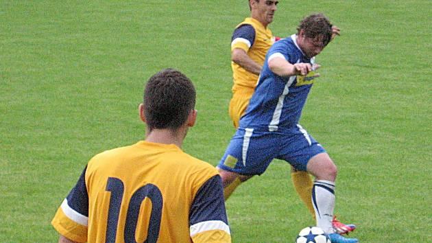 Sedleckoprčického Pavla Müllera (v modrém) nahání jediný střelec zápasu divišovský kapitán Martin Vávra.