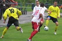 Votický střelec třetího gólu Faitl dorážel na domažlického Paula. Souboji přihlíželi domácí Očovan (č. 18) a  Hudec (č 10).