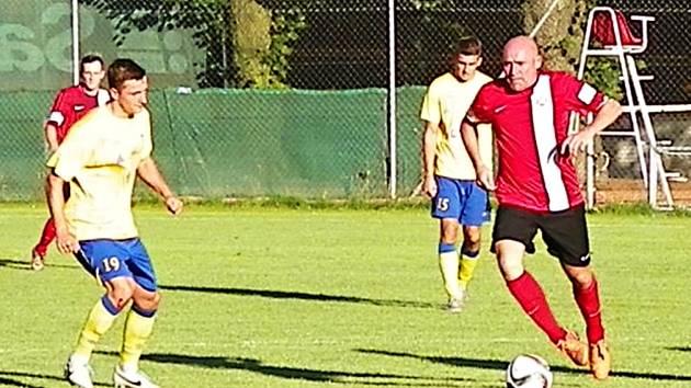 Fotbalového básníka a bývalého reprezentanta Jiřího Štajnera (u míče) v dresu Chrastavy, sledoval benešovský David Skopec.