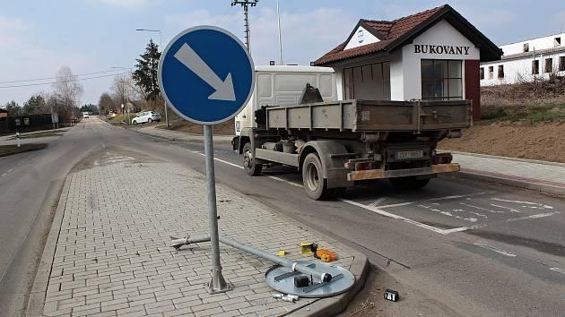 Poničená dopravní značka na ostrůvku  mezi autobusovými zastávkami v Bukovanech.
