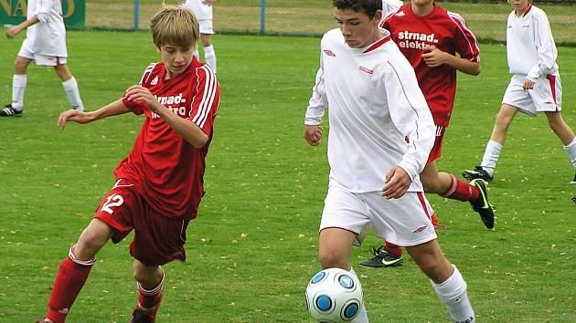 Aleš Strnad, útočník starších žáků Benešova (v bílém) sledovaný sedlčanským Lukášem Housou, se v závěru zápasu zranil.