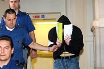 Pachatelům závažných trestných činů bývá u soudu přítomnost fotografů nepříjemná.