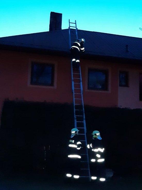 Hasiči zajišťují poškozenou střechu rodinného domu.