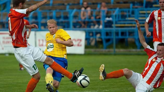 Dominik Němec střílí druhý gól Benešova do sítě Malše Roudné. Hostující bloky hráčů přišly pozdě.