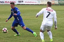 Vlašimský Tomáš Wiesner (v modrém) odehrává míč před střelcem Ústí Lukášem Poučkem.