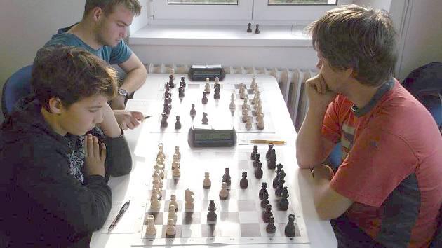 Momentka z derby Sázava - Brodce B. K vysokému vítězství hostů přispěli na prvních dvou šachovnicích talentovaní mladíci. David Zvolenský (u okna) remizoval s Jiřím Kotzotem, vedle něj pak Vojtěch Dudek porazil Filipa Daneše.