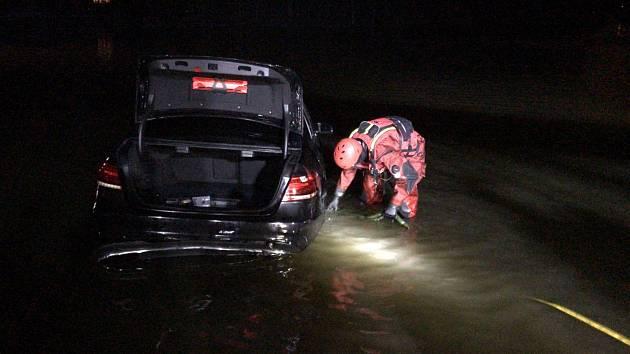 Hasiči lovili osobní vozidlo ze dna Jevanského rybníka.
