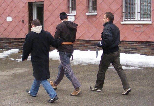 Eskorta jednoho z pachatelů do pražské cely předběžného zadržení. O vazbě se rozhodne ve čtvrtek