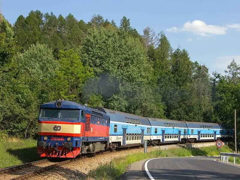 Osobní vlak 9066 na čele patrových vozů. Lokomotiva Zamračená či Bardotka 749 121-0 projíždí po trati 210 mezi zastávkou Krhanice a zastávkou Prosečnice.