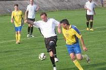 Souboj veteránů. Devětačtyřicetiletý Milan Ottl z Teplýšovic (v bílém) si kryje míč před hrajícím trenérem Týnce Radkem Skálou.