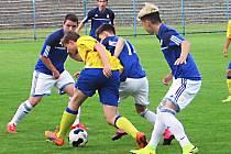Benešovský obránce Petr Horák (ve žlutém) se v zápase sedmnáctek snaží prosadit před motorletský trojblok.