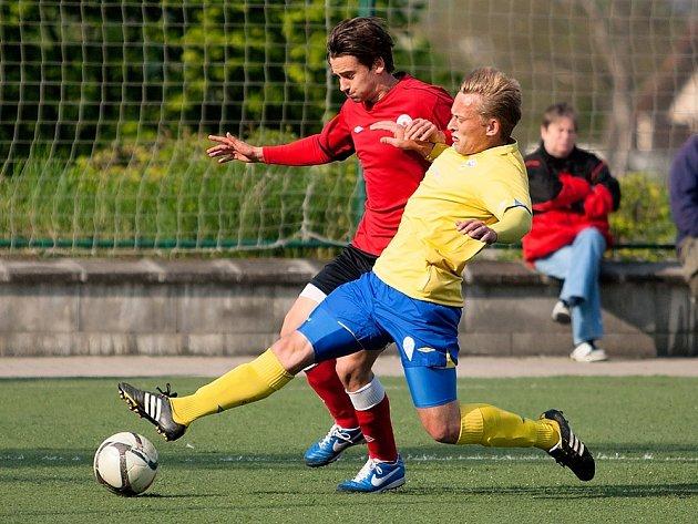Benešovský Oldřich Komárek se snaží skluzem zastavit bývalého hráče Benešova Josefa Petličku, tentokrát v dresu Ostré.