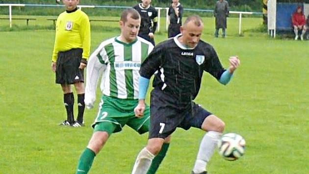 Kamil Kulhavý z Nespek si zpracovává míč sledován skalickým hráčem.