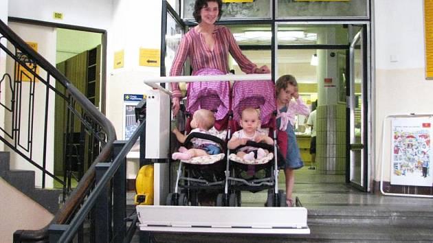 Mladá maminka s dvojčátky v kočárku a dalším malým dítětem po boku vyzkoušela funkčnost hydraulické bezbariérové plošiny v budově České pošty