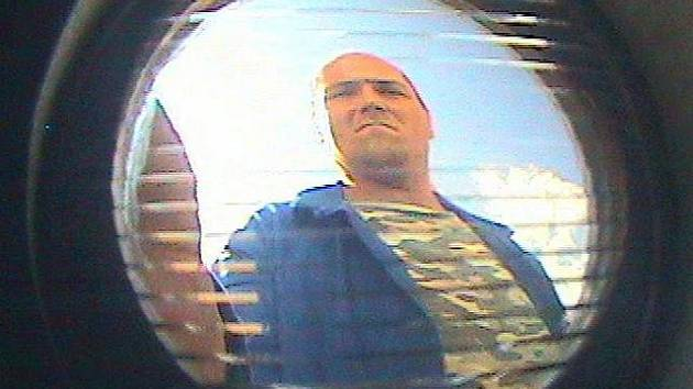 Záznam z kamerového systému, kde je zachycený podezřelý muž při výběru peněz z bankomatu v Neveklově.