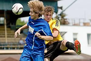 Benešovský starší dorostenec Karel Vacek (v modrém) byl dříve u míče ve vzdušném souboji než brandýský hráč.