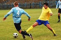 Benešovský Martin Prikner (ve žlutém) se snažil obrat o míč obránce béčka Sezimova Ústí.