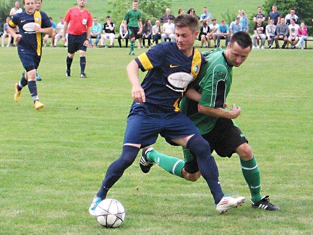 Střelec čtvrté branky Divišova Petr Campodonico (v modrém) si kryje míč před struhařovským Petrem Koblasou.