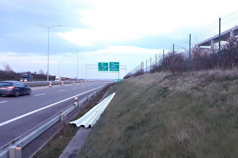 Pražský okruh D0-uvolněná část střešní krytiny za svodidly mimo těleso dálnice.