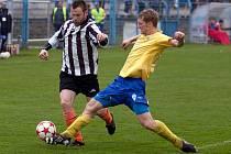 Benšovský David Zoubek (ve žlutém) vypichuje míč kolovečskému Tomáši Doškovi.