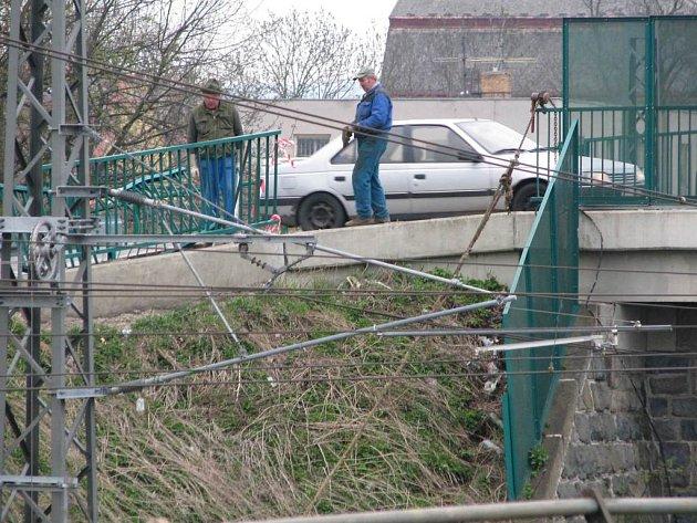 Opraváři najatí na tuto práci SÚS Benešov vyměňují zábradlí