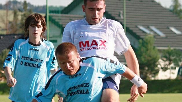 V zápase Olbramovic s Jírovicemi musel Tomáš Helma (v modrém) často odolávat atakům Tomáše Sahuly.Ten se však golově neprosadil.