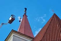 Umisťování restaurované zlacené makovice a kříže na věž kostela sv. Vojtěcha v Jílovém u Prahy.