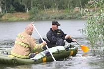 Pátrání policistů a hasičů na hladině rybníka.