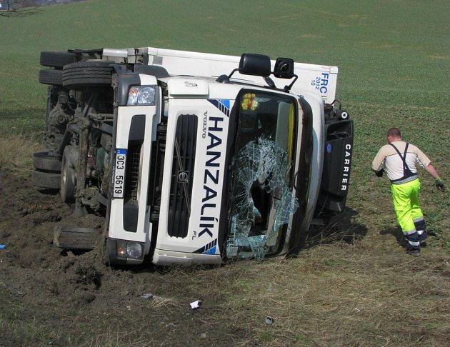 Nákladní auto vyjelo vlevo z vozovky do stráně a  převrátilo se do pole