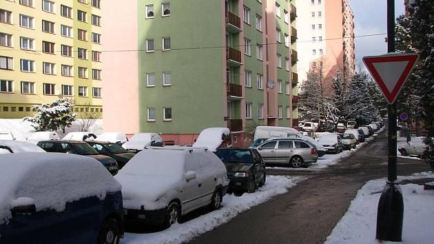 Bezručova ulice. Auta mají podle značky Obytná zóna parkovat jen na vyhrazených místech, tím je značka Zákaz stání zbytečná. K Dej přednost v jízdě není vyznačená hlavní silnice.