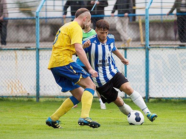 Kapitán Benešova Luboš Braný (ve žlutém) sleduje co provede s míčem domažlický hráč.