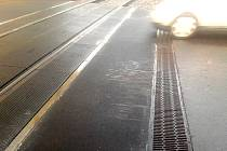 Železniční přejezd se stopami projíždějících aut.
