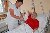 Sestra vysvětluje pacientce ovládání elektricky polohovací postele.