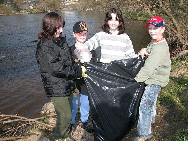 žáci při úklidu řeky.