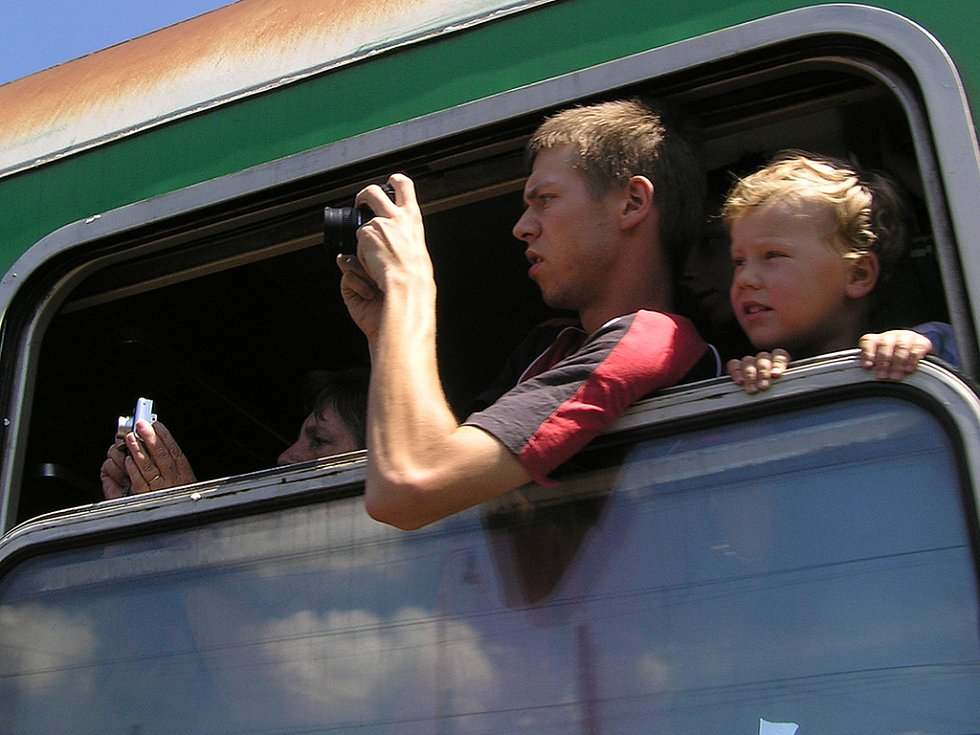 Zvědaví cestující z projíždějícího vlaku