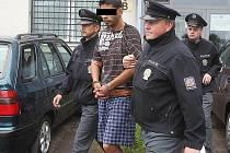 Kolínští policisté eskortují pětadvacetiletého muže do vazby.