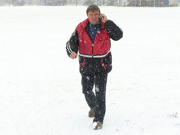 Rozhodčí Josef Hocek se prochází na zasněženém hřišti.