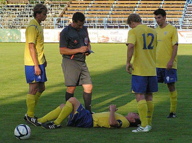 Hráči Benešova se s rozhodčím Rybkou sklánějí nad Martinem Turkem, jehož faul píseckého Janů vyřadil ze hry.