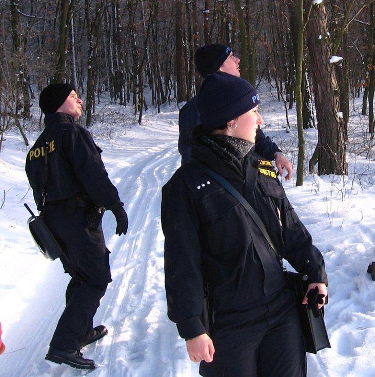Rozcestí Pod Borkou. 12. ledna 10.20, policisté míří přes zasněženou louku k Borce, rekreačním objektům nedaleko Přestavlk u Čerčan