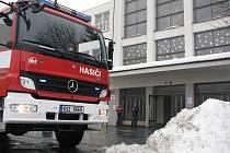 Benešovští hasiči řeší situaci na střeše školy.
