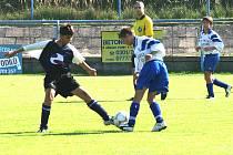 Týnecký Jakub Müller (vpravo) se přetlačoval o míč se sedleckoprčickým Tomášem Kotvou. Souboj starších žáků bedlivě sledoval hlavní rozhodčí Velebil
