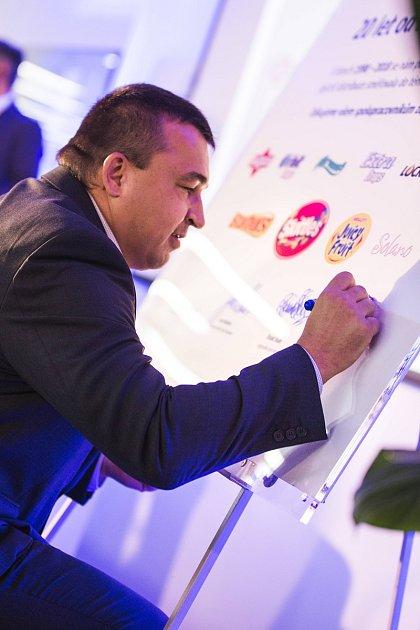 Michal Říha, ředitel továrny Mars Wrigley Confectionery vPoříčí nad Sázavou, podepisuje slavnostní plaketu upříležitosti 20.výročí založení továrny.