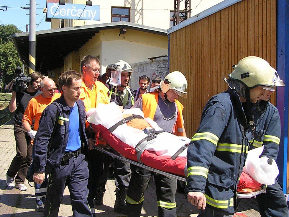 Hasiči odnášejí zraněného účastníka nehody