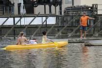 Brodecký jez, prázdniny 2015. Muž na pilíři vorové propusti ukazuje dívkám v lodi, kudy najet na vodáckou skluzavku.