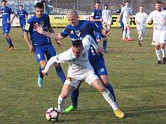 Nikolas Šumský z Frýdku-Místku (v bílém) si kryje míč před vlašimským Adamem  Kučerou.