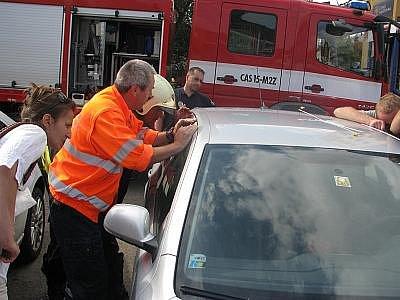 Přivolaný zdravotník přes sklo auta kontroluje chlapcův zdravotní stav.