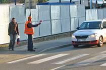 Muži v Čechově ulici dohlíží na bezpečnost přecházejících chodců.